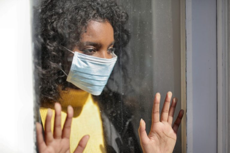 looking out the window wearing facemask lockdown quarantine